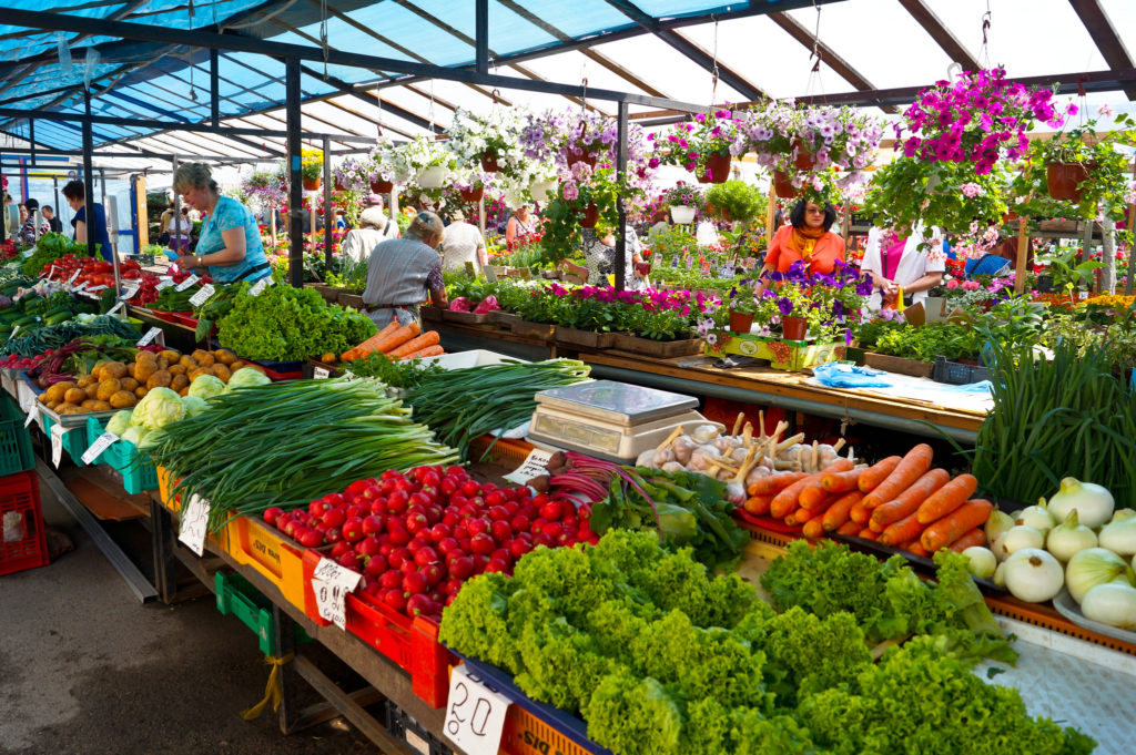 An open-air street market with vegetables: spring onions, lettuce, onions, carrots, garlic, oranges, cabbage and, in the background, pots of flowers.