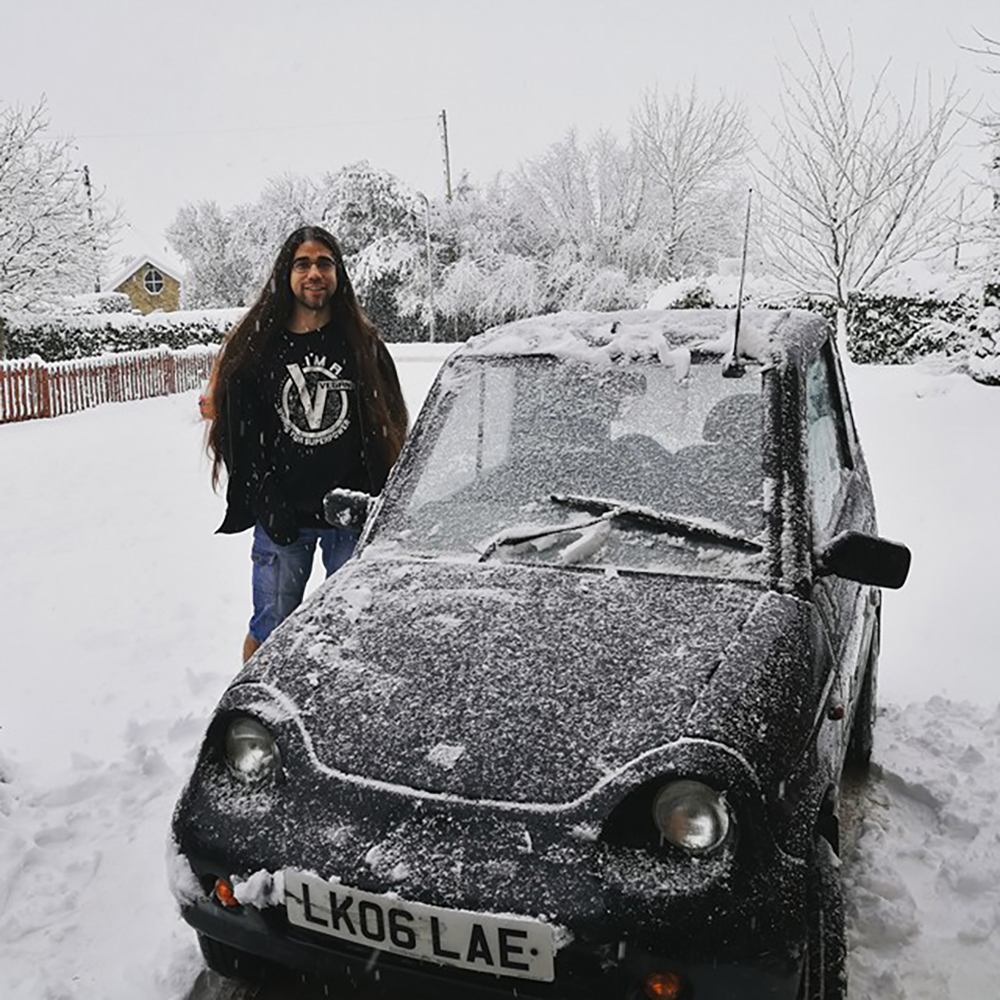 A thin, bearded man with long, straight, brown hair, wearing a black T-shirt and jeans, stands beside a small, black car. They are in a backyard, with some trees and shrubbery in the background. Everything is covered in clean, white snow. The car, however, has only a light dusting, as if recently shovelled out and brushed off. Some snowflakes are still falling.