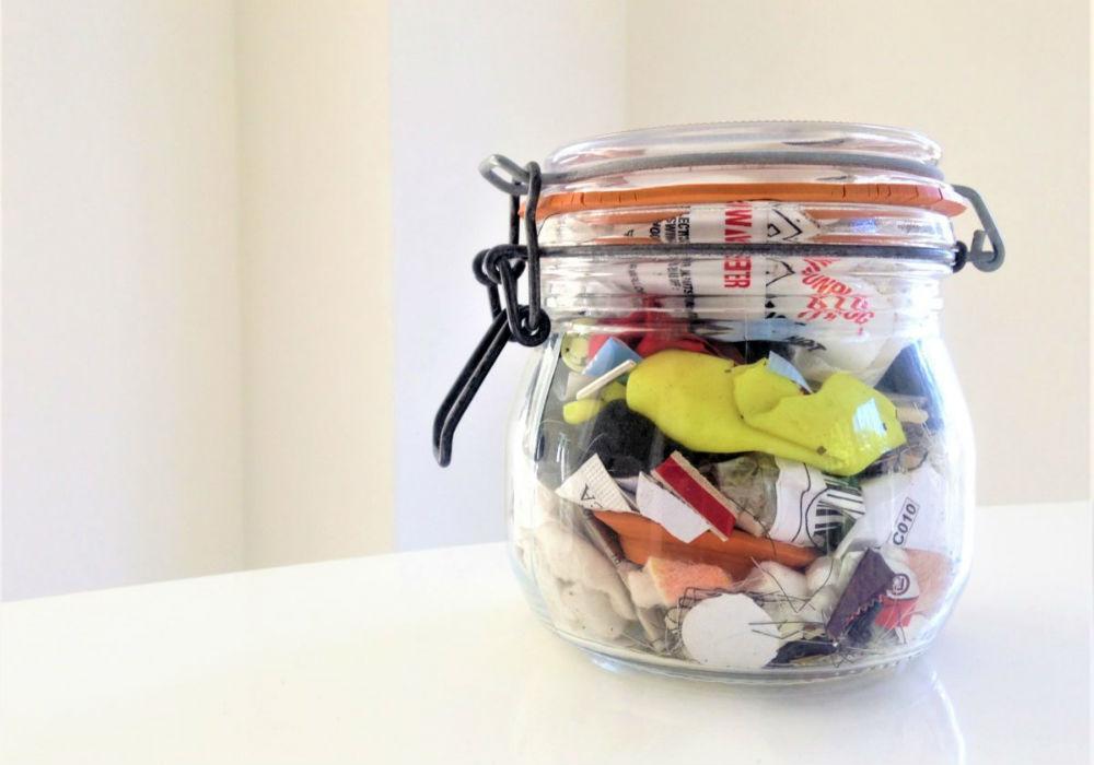 Close de um pote de vidro pequeno, fechado, com algumas embalagens plásticas.