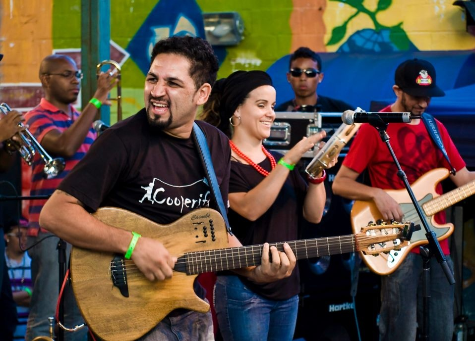 On the left is a dark-haired man with a goatee. He is holding a guitar and looking to the left. Next to him is a white woman with brown hair wearing jeans and a black T-shirt. She is playing the tambourine and smiling. Next to her is a thin man, wearing jeans, a red shirt and a cap. He is looking down and playing the bass. Two other musicians, behind them, play some sort of percussion instruments.