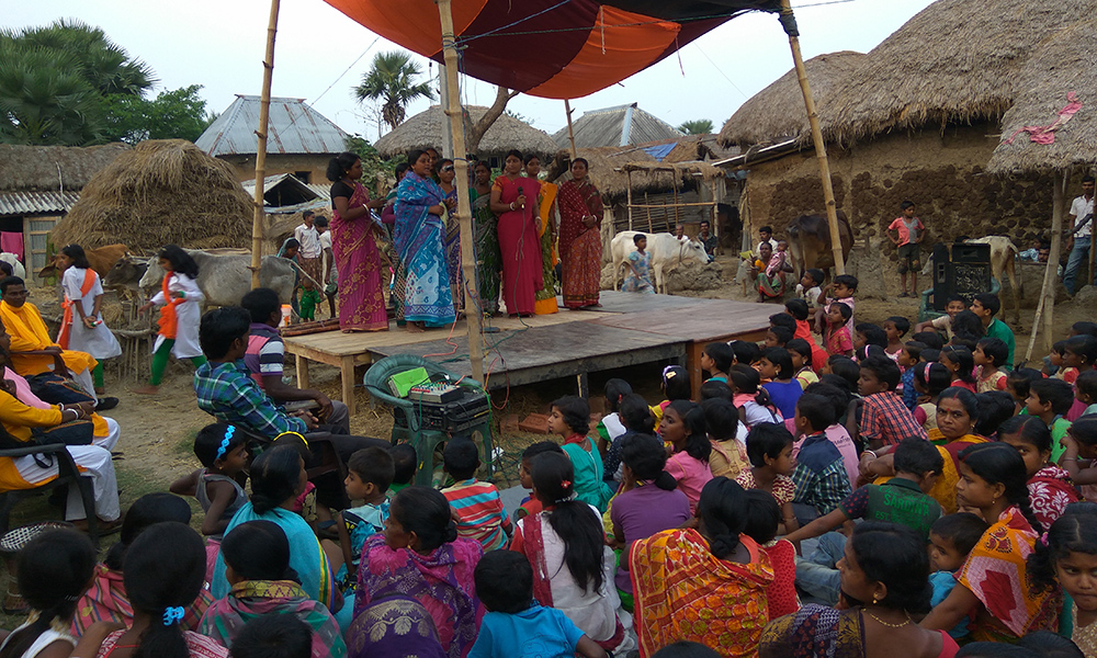 There are seven Indian women wearing long and colorful sarees (typical dresses of their culture) standing on a makeshift wooden podium covered by a canvas roof. In the foreground, women and children, their backs to the camera, face the podium, sitting and watching. In the background are several houses and huts made of clay, some with thatched roofs.
