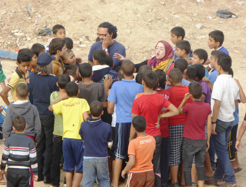 The man described previously is surrounded by children. Next to him is a white woman wearing a scarf on her head, gesturing and speaking, perhaps singing. In the background, parched-looking dirt and rocks.