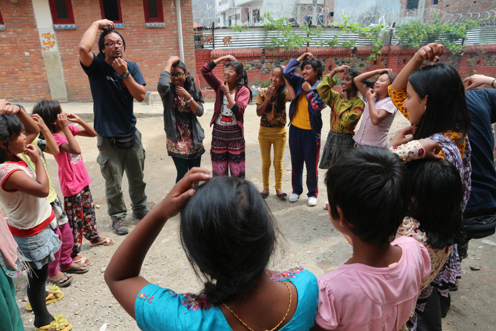 The same man described in the previous photo stands in a circle with several brown-skinned, black-haired children. They seem to be playing a mimicking game: the kids are looking at and imitating the man, whose right hand scratches his forehead while his left hand scratches his chin.
