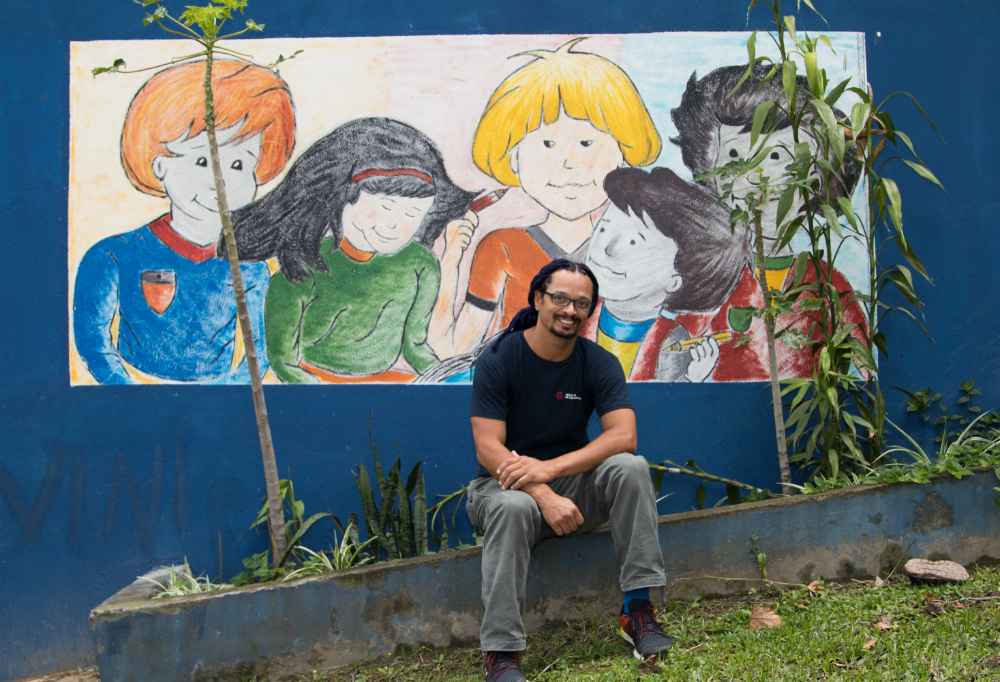 The man described previously is sitting on a short wall, his feet resting on a green lawn. In the background, a mural depicts children with orange, black and yellow hair.