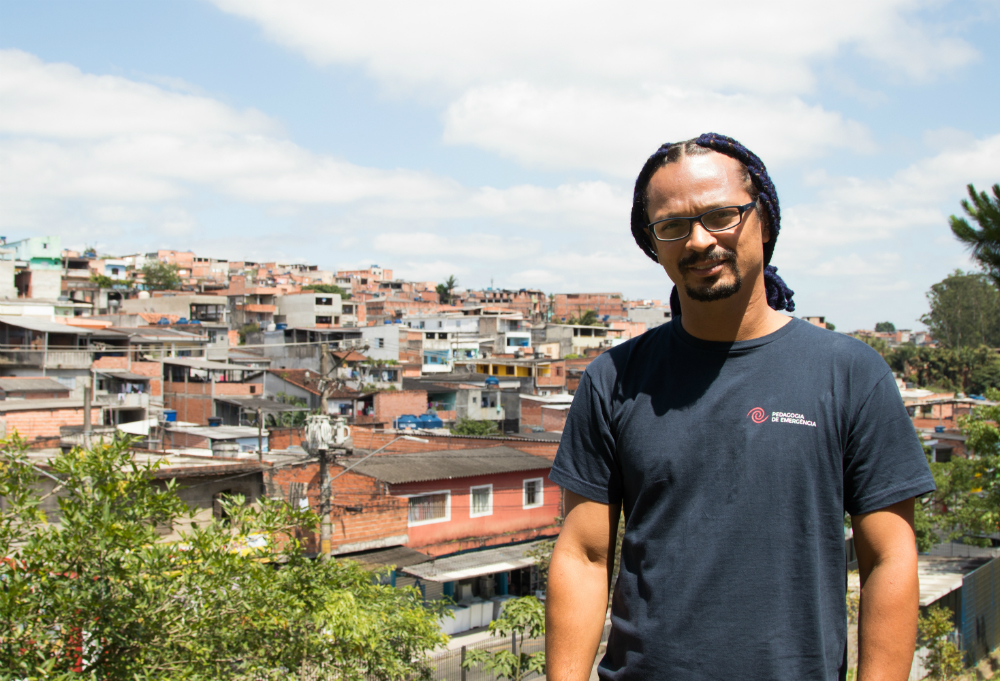 A black man, with long, black, braided hair and a goatee, wearing glasses and a black T-shirt, looks at the camera. In the background are several small, simple houses. It is a suburban neighborhood.
