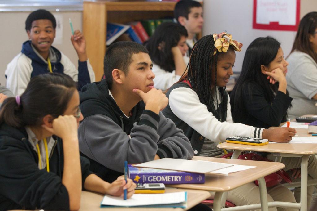 Um grupo de oito estudantes está sentado em carteiras dispostas em duas fileiras horizontais, escrevendo em folhas de papel e com livros de Geometria.Todos eles têm etnias diferentes: negros, pardos, brancos e orientais.