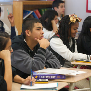 Un grupo de ocho estudiantes está sentado en carteras dispuestas en dos filas horizontales, escribiendo en hojas de papel y con libros de Geometría. Todos ellos tienen etnias diferentes: negros, pardos, blancos y orientales.