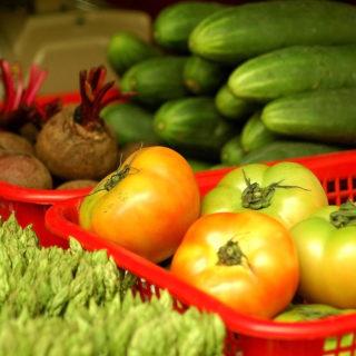La foto muestra verduras, en plano cerrado. En primer plano, aparece la parte superior de algunas hojas; en segundo plano, una canasta roja con tomates un poco verdes, al lado, remolacha; en tercer plano, hay pepinos apilados y parte de dos bandejas.