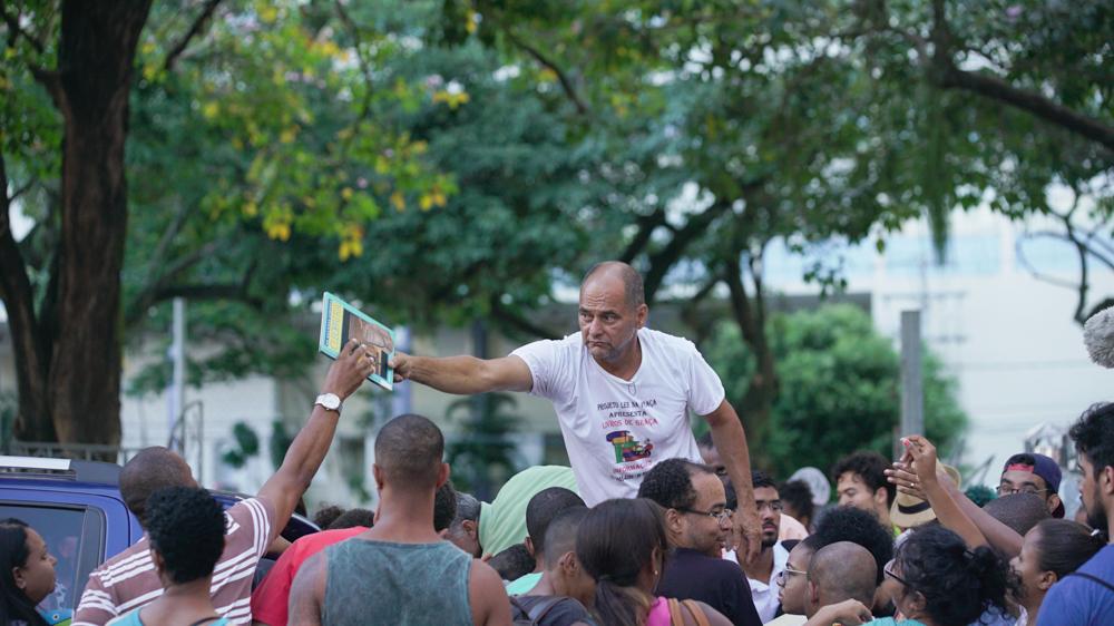 Un hombre blanco, calvo, usando una camiseta blanca, está en el medio de una multitud, en un nivel un poco más alto (parece estar encima de un taburete) distribuyendo libros. En la imagen, le da el libro a otro hombre negro (no podemos ver su cara).