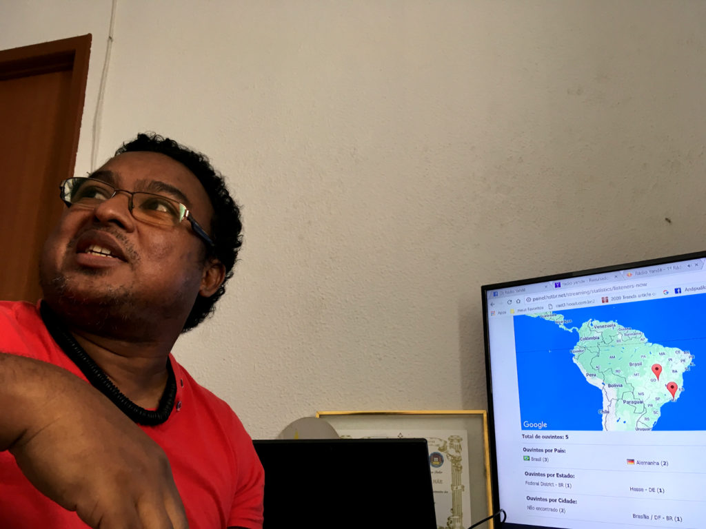 A 43-year-old dark-skinned man with wavy, black hair in front of a computer monitor. On the screen, a map of Brazil is displayed.