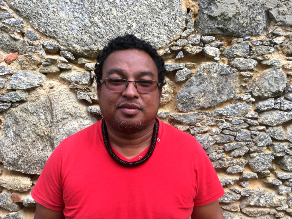 A 43-year-old dark-skinned man with wavy, black hair. He wears a red T-shirt, a necklace of wooden beads and glasses. He stands in front of a stone wall.