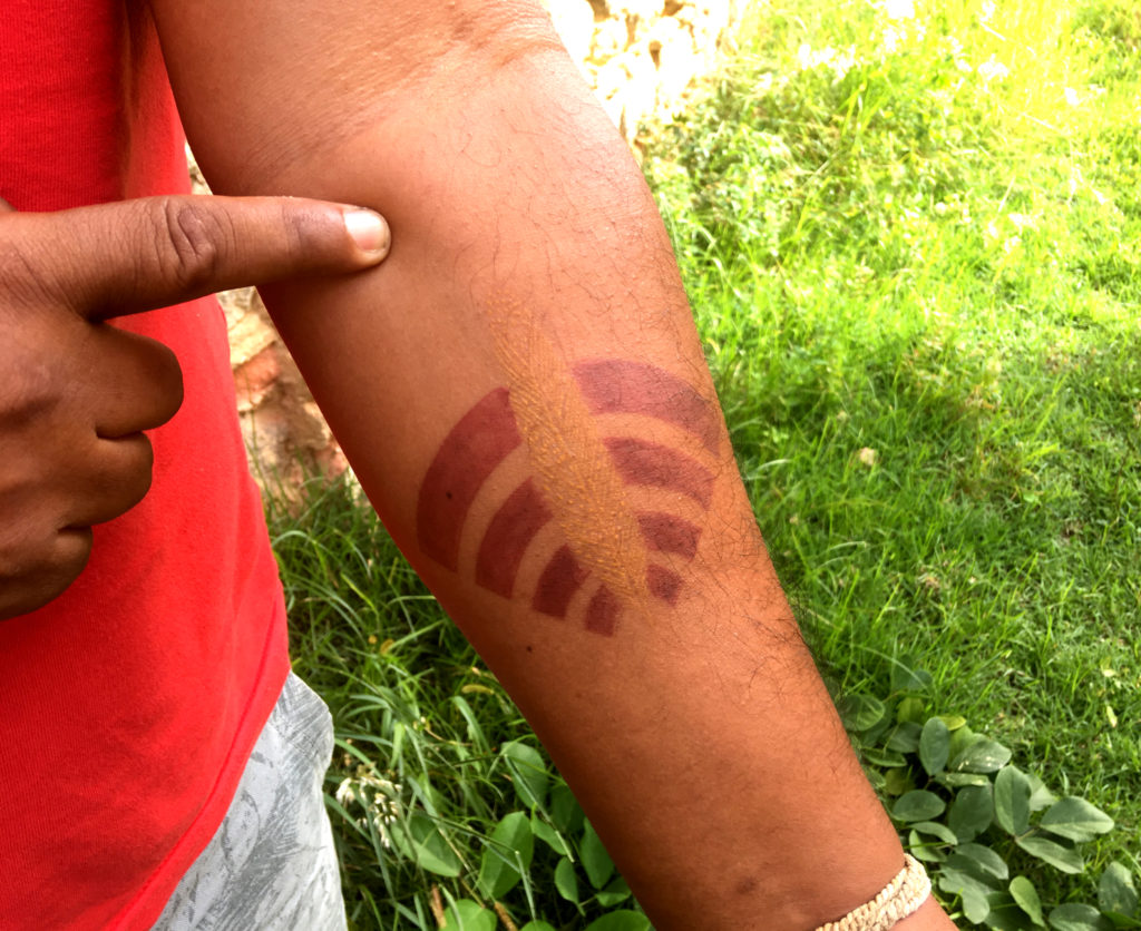 The inner side of a person's forearm with a tattoo, in yellow and red, representing an indigenous headdress.