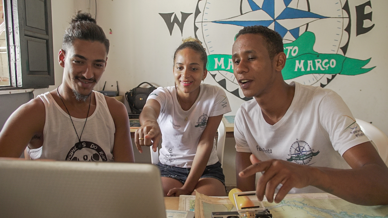 """Three young, light-skinned black people sit at a wooden table, with maps and a laptop. They are looking and pointing at the laptop's screen. The young man, in the left side of the photo, has a goatee and wears his hair tied back. In the center is a young brunette with curly hair, also tied back. She wears a white t-shirt with a compass logo on it. On the right side of her is a thin young man with short hair, wearing the same t-shirt as the woman, with the words legible: """"Maré de Março."""" Behind them, on the wall, is a much larger rendition of the same logo, and the same words although those words are partly hidden by the thin young man's head."""