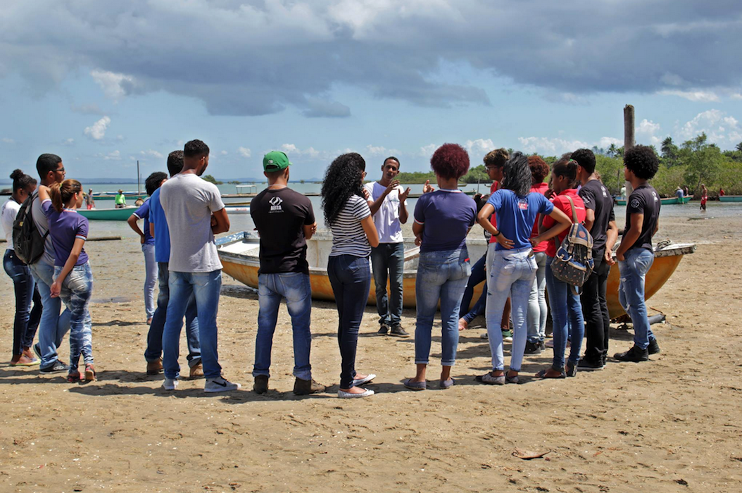 A thin young man is standing on a beach, with sea and boats in the background, speaking to a group of young people (all with their backs to the camera, looking at him).