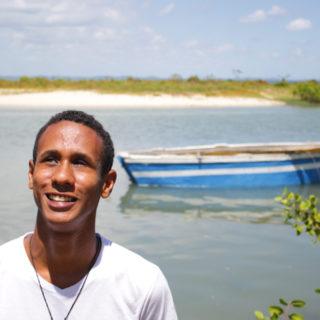 Um homem negro, magro, de cabelos curtos e crespos, vestindo camisa branca, está olhando para o céu e sorrindo (no canto esquerdo da foto). Atrás dele, à direita, está o mar, uma faixa de areia e uma pequena canoa nas cores branco e azul.