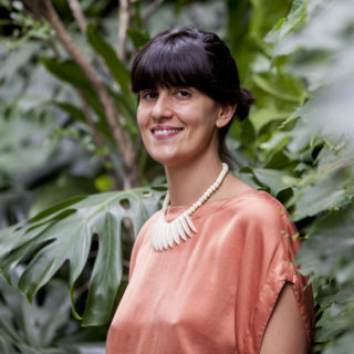 A white woman, with straight black hair, tied back, with bangs. She is wearing a salmon-colored shirt and a necklace made of white stones. She smiles at the camera. Her body is turned slightly to the left side of the picture. In the background are some plants with large green leaves.