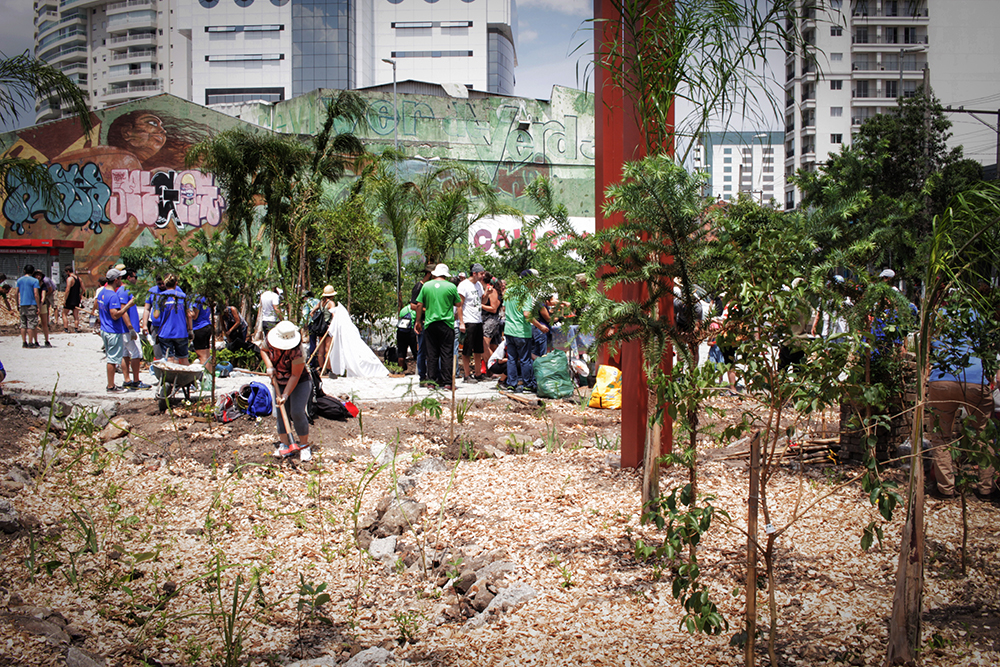 A lot on which groups of people have gathered. A person in a cream-colored hat tends the soil. There is some sawdust on the ground and some young trees have been planted. In the background are several buildings and a wall covered in graffitti.