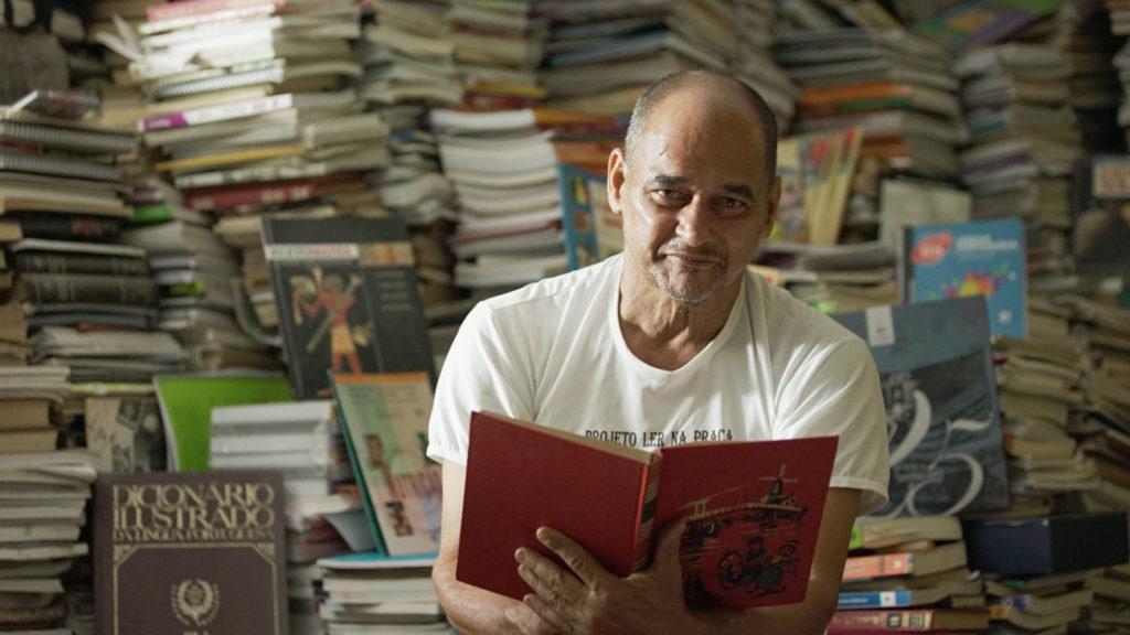 Un hombre blanco, anciano, calvo, está sosteniendo un libro abierto de capa roja y mirando a la cámara. Detrás, hay una gran montaña de libros, que aparecen borrosos, cubriendo todo el fondo de la imagen.