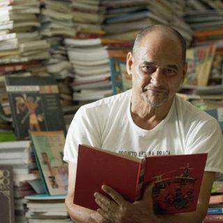 Um homem branco, idoso, careca, está segurando um livro aberto de capa vermelha e olhando para a câmera. Atrás, há uma grande montanha de livros, que aparecem desfocados, cobrindo todo o fundo da imagem.