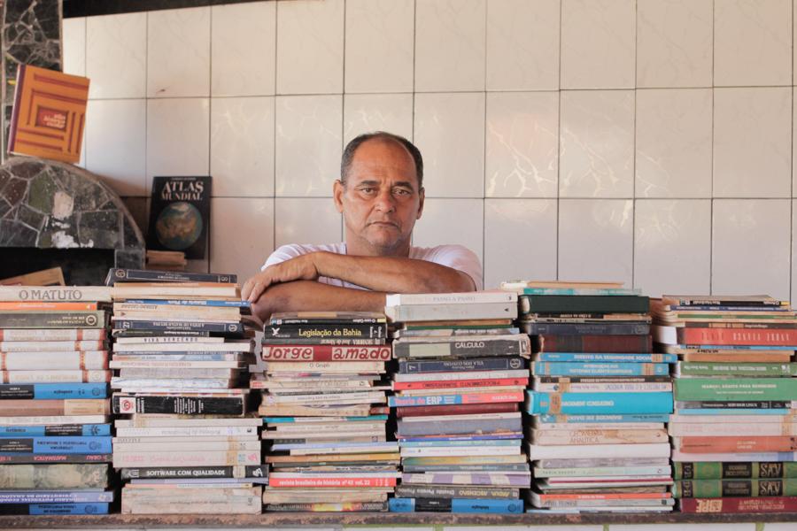 Un hombre blanco, calvo (parte de su pelo gris aparece alrededor de la cabeza) está serio, mirando a la cámara, con los brazos apoyados en varias pilas de libros que están en el mostrador al frente de él. Los libros cubren casi toda la imagen y sólo podemos ver su cara y sus brazos cruzados apoyados en los libros.