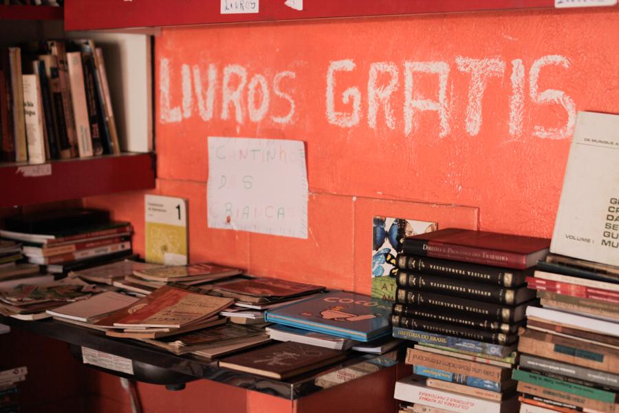 """La imagen muestra una pequeña mesa y parte de una biblioteca con varios libros y, en la pared naranja, dice """"Libro Gratis"""" con tiza blanca."""