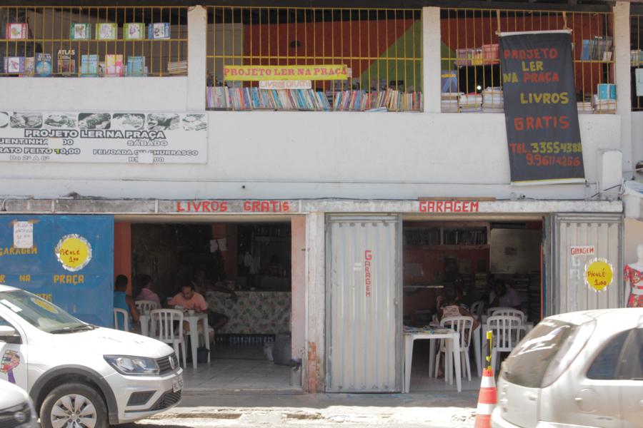 """La imagen muestra un establecimiento comercial de dos plantas: en la planta baja están las dos puertas abiertas, con algunas mesas y sillas de plástico, donde parece funcionar un restaurante. En la parte superior, se pueden ver estantes con libros. El lugar tiene carteles y frases repartidos en las paredes exteriores como """"Libro Gratis"""" y """"Projeto Ler na Praça"""", que en español significa Leer en la Plaza."""