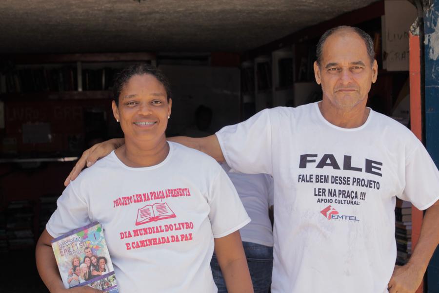 La imagen muestra una mujer negra con pelo atado (lado izquierdo de la foto) sosteniendo un libro con su mano izquierda, al lado, un hombre blanco y calvo está con una de las manos en sus hombro. Ambos miran a la cámara y sonríen tímidamente.