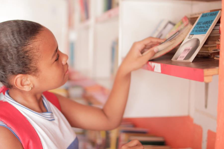 Una chica negra con pelo atado (esquina izquierda de la imagen) está mirando un estante de libros. La imagen aparece en plano cerrado y en el fondo se ve un estante de libros (esquina superior derecha de la pantalla), pero fuera de foco.