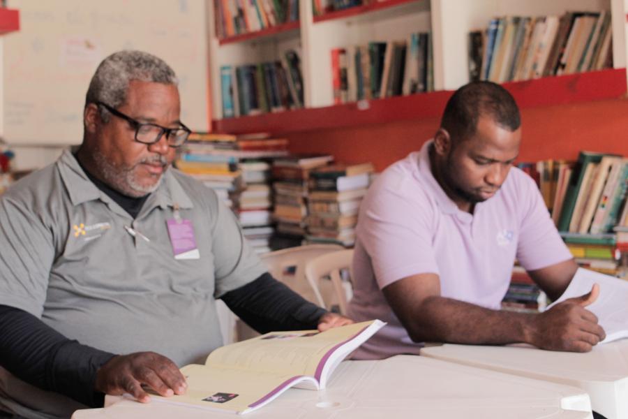 Dos hombres negros están sentados en una mesa leyendo libros - al fondo una biblioteca llena de libros. El primero (lado izquierdo de la foto) tiene pelo y barba con canas, usa gafas y camisa gris y tiene una complexión un poco más gruesa. El otro (lado derecho), usa camisa salmón y tiene pelo negro rapado.