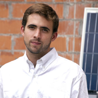 A young white man with light brown hair and a white shirt, in front of an exposed brick wall. To the right of him is a solar panel.