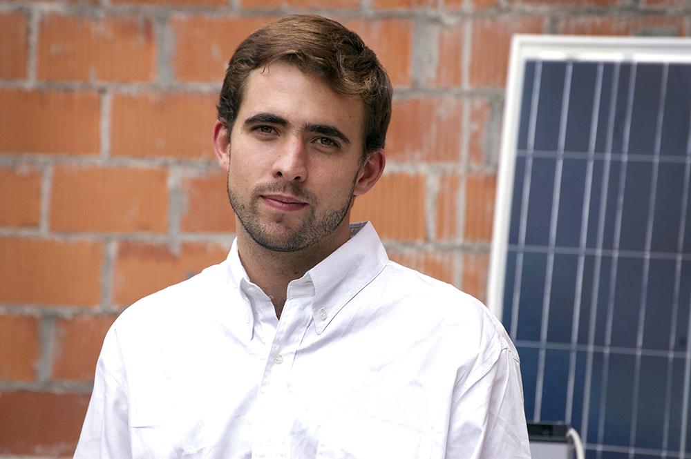 Um homem jovem, com cabelos castanhos claros, de camisa branca, em frente a uma casa com tijolos expostos.