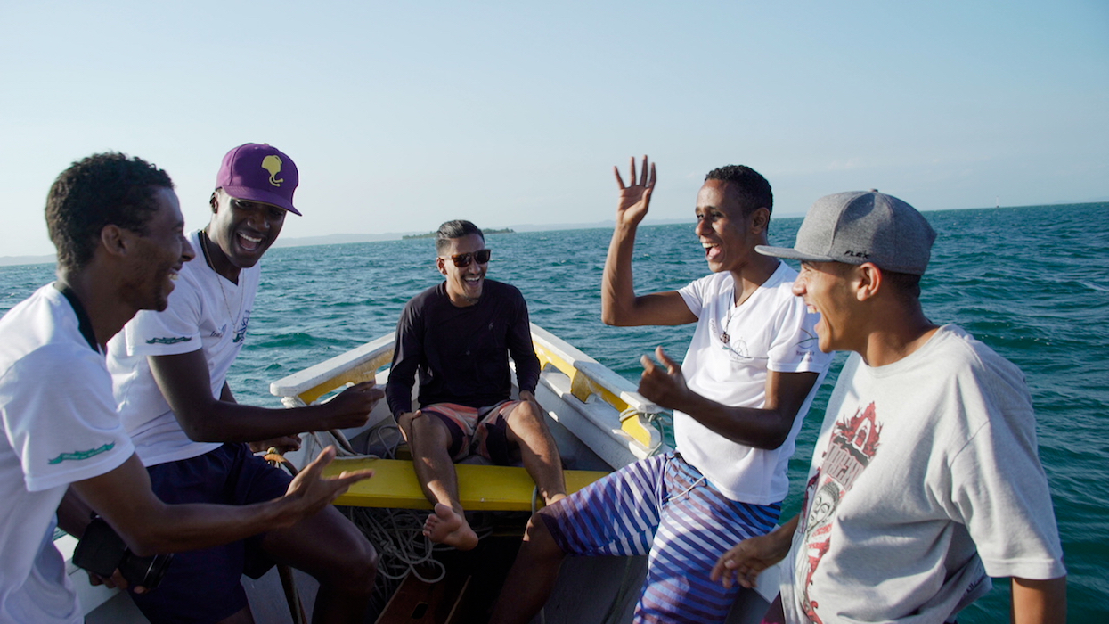 A group of 5 young black people on a boat, laughing and gesturing. Behind them, sea, sky, and, in the distant background, an island, and some other land forms which are difficult to see.