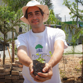 "A short, white, gray-haired man wears a beige hat and a white shirt bearing the words, ""Floresta de Bolso"". He is smiling, holding a seedling. He makes a gesture toward the camera, as if offering the plant to the viewer. Behind him are some young trees and bricks in a square."