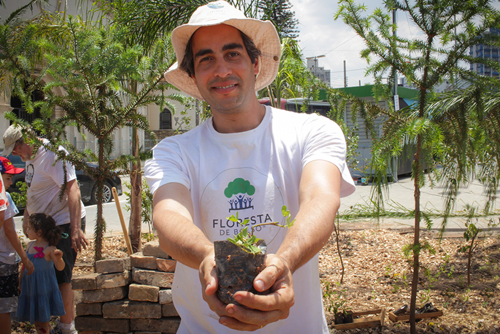 """A short, white, gray-haired man wears a beige hat and a white shirt bearing the words, """"Floresta de Bolso"""". He is smiling, holding a seedling. He makes a gesture toward the camera, as if offering the plant to the viewer. Behind him are some young trees and bricks in a square."""
