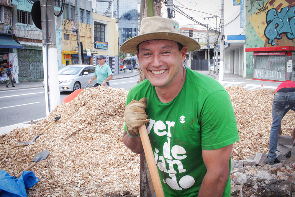 A white man with a sweaty face is wearing a cloth hat and a green T-shirt. He is smiling at the camera and holding a hoe (we only see the handle). Behind him are some concrete blocks and piles of sawdust.