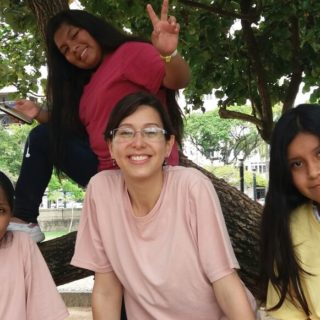 A woman with her hair tied back, wearing glasses and a pink t-shirt, is surrounded by three teenage girls, one of whom is sitting in a tree behind the woman, making a peace gesture with her fingers.
