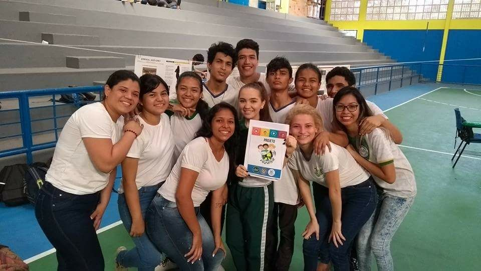 """Um grupo de estudantes reunidos em uma quadra poliesportiva. Uma das jovens está segurando o panfleto do projeto """"Voz Ativa"""""""