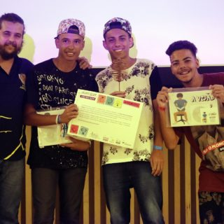 "The photo shows a white man with a beard, his hair tied back, wearing a black t-shirt and jeans, next to three teenage boys. The first boy is wearing a patterned baseball cap, a black t-shirt with words printed on it in white, and jeans. He is holding the Design for Change certificate. Next to him is another teenage boy. This one is wearing a patterned baseball cap, a white t-shirt with a black pattern, and jeans. The last boy, on the right, wearing a brown t-shirt and black pants, is smiling and holding the ""Viewed through Rap"" curriculum."