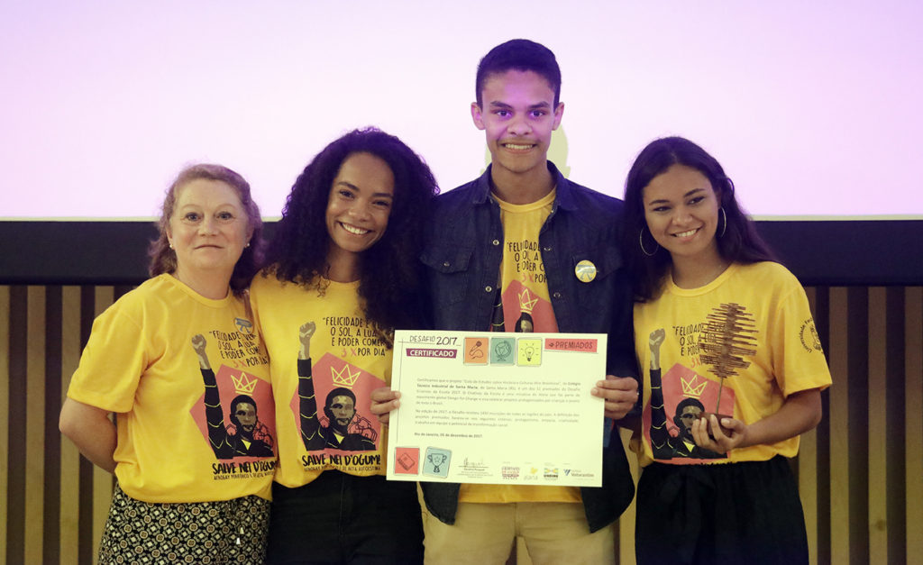 Four people stand side by side, each wearing a yellow t-shirt showing an image of a black man holding up his right fist. On the left end is an older white woman with light brown hair. Next to her is a young black woman with long curly hair. Beside her is a young black man, much taller than everyone else in the photo, holding a certificate. And on the right end is a young black woman with straight, dark brown hair, wearing hoop earrings.