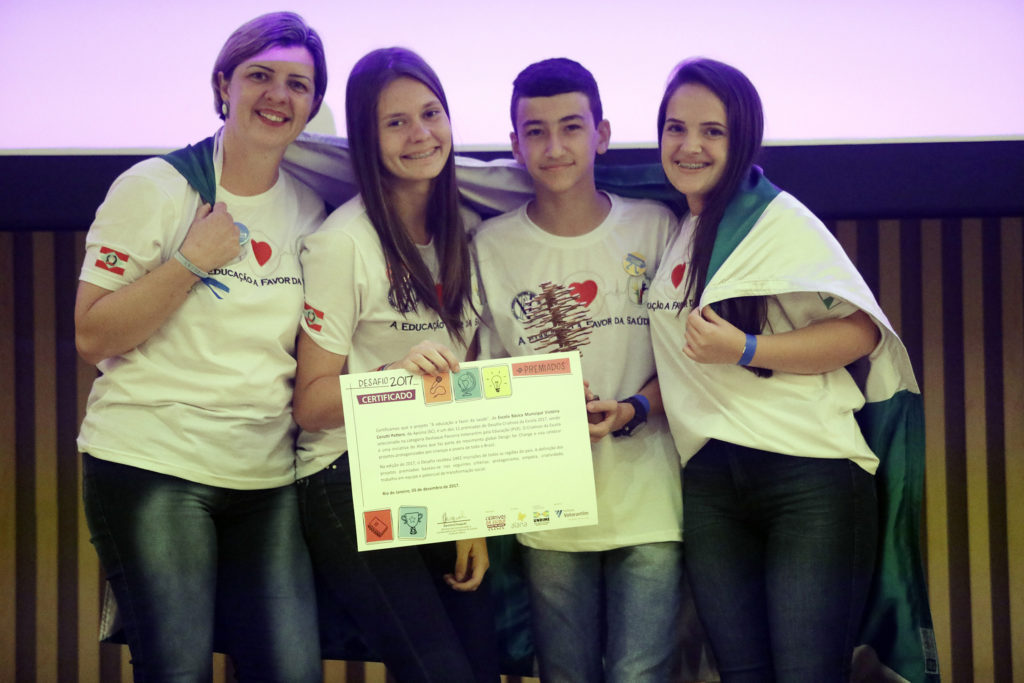 The photo shows four people, all wearing jeans and white t-shirts with the same design. On the left is a white woman with short light brown hair. To her right, a teenage girl with long brown hair holding a certificate. Next to her, a teenage boy with short dark hair. And on the right is a teenage girl with long dark hair. All four of them are wrapped in a green and white flag.