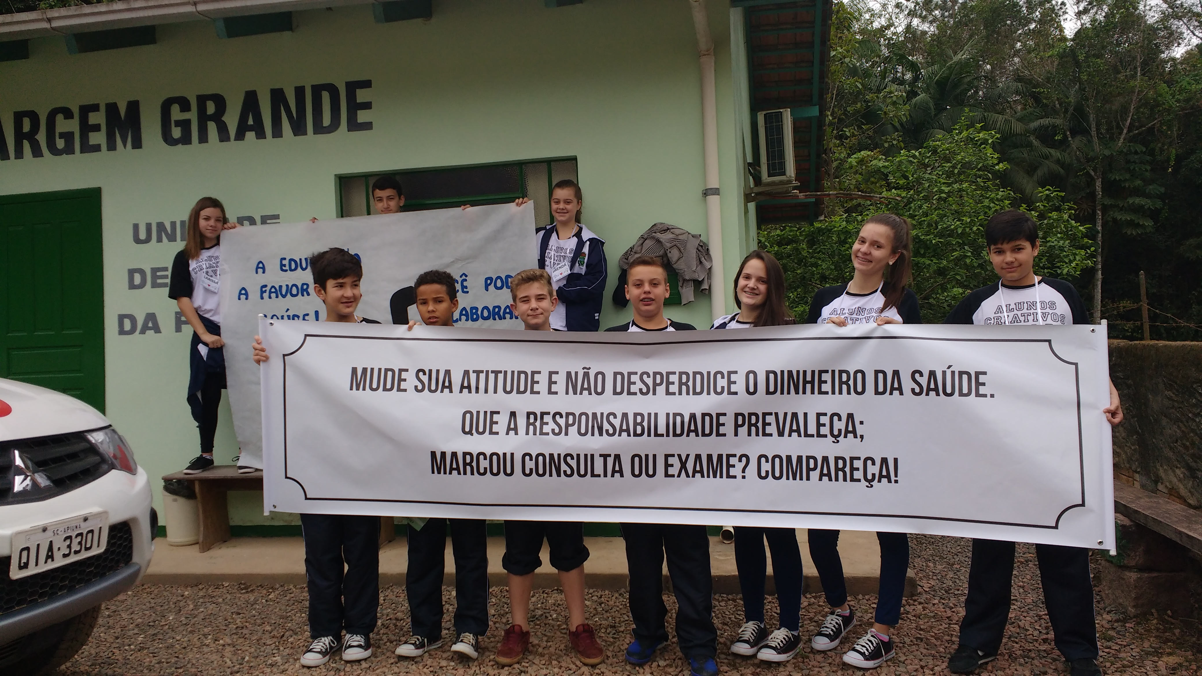 "A group of teenagers holds a banner that says, in Portuguese, ""Change your attitude and don't waste public money. Take responsibility: Did you schedule an exam? Show up!"""