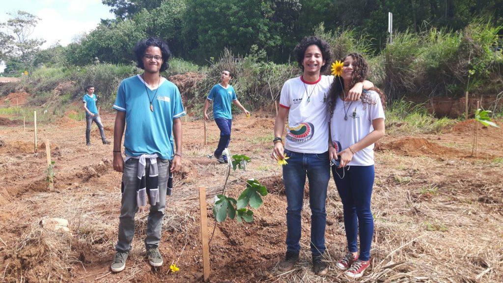 La foto muestra a tres jóvenes de frente - el primero, a la izquierda, con camiseta azul y pantalón jean; a su derecha un chico y una chica, ambos con camiseta blanca y pantalón jean - y dos al fondo - con camiseta azul y pantalón jean. El suelo es de tierra y hay algunos esquejes plantados. Al fondo se ve un bosque espeso.