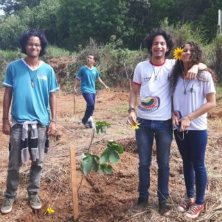 Three teenagers stand in the foreground. One boy is wearing a blue t-shirt and jeans. The other two, a boy and a girl, each wear a white t-shirt and jeans and stand close together, his arm draped around her shoulders, a yellow flower in her hair. Behind them are two more teenagers wearing blue t-shirts and jeans. The young people are standing on dirt, some saplings planted around them. In the background is a dense forest.