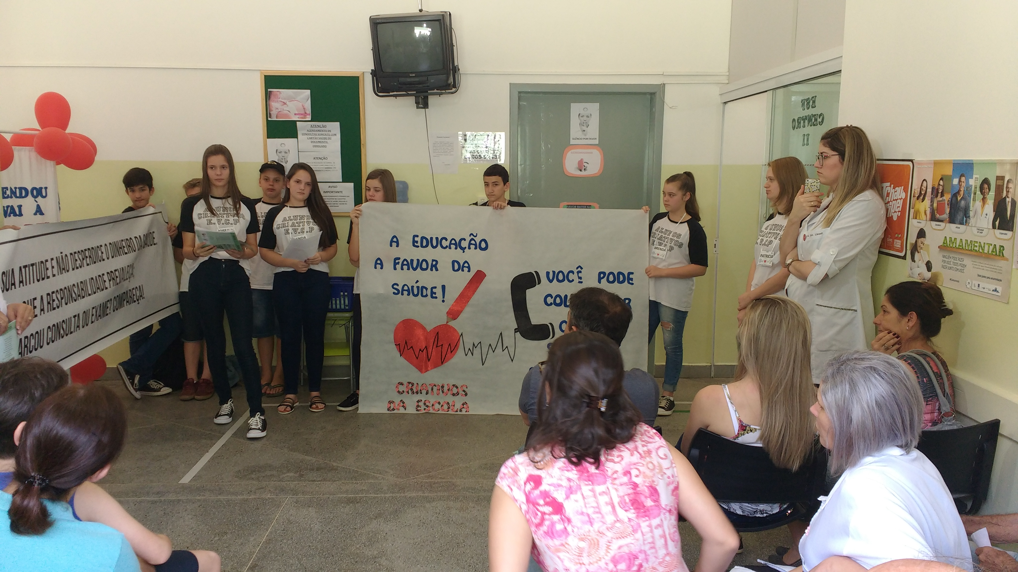 A group of teenagers holds up two big posters in front of a classroom, making a presentation to an audience of adults, who are sitting on chairs.