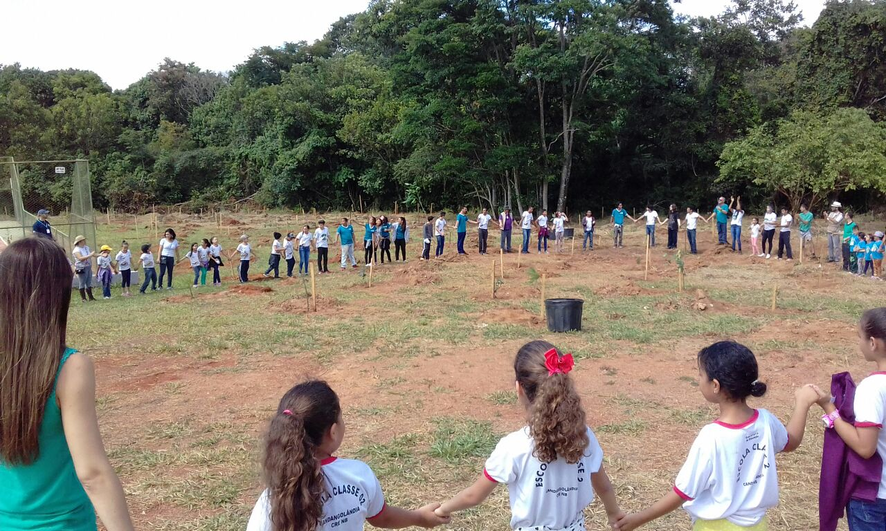A large circle of children holding hands, standing on dirt with some grassy spots. In the background, a forest.
