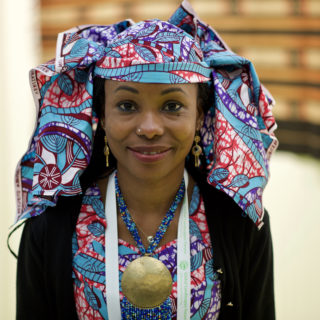 A black woman is wearing a blue necklace with a large golden medallion and, on her head, a blue, purple, red and white print scarf. She is also wearing a shirt or dress that matches her colorful scarf, and over it, a black sweater. She is smiling at the camera. She is in the center of the photo, with the background out of focus.