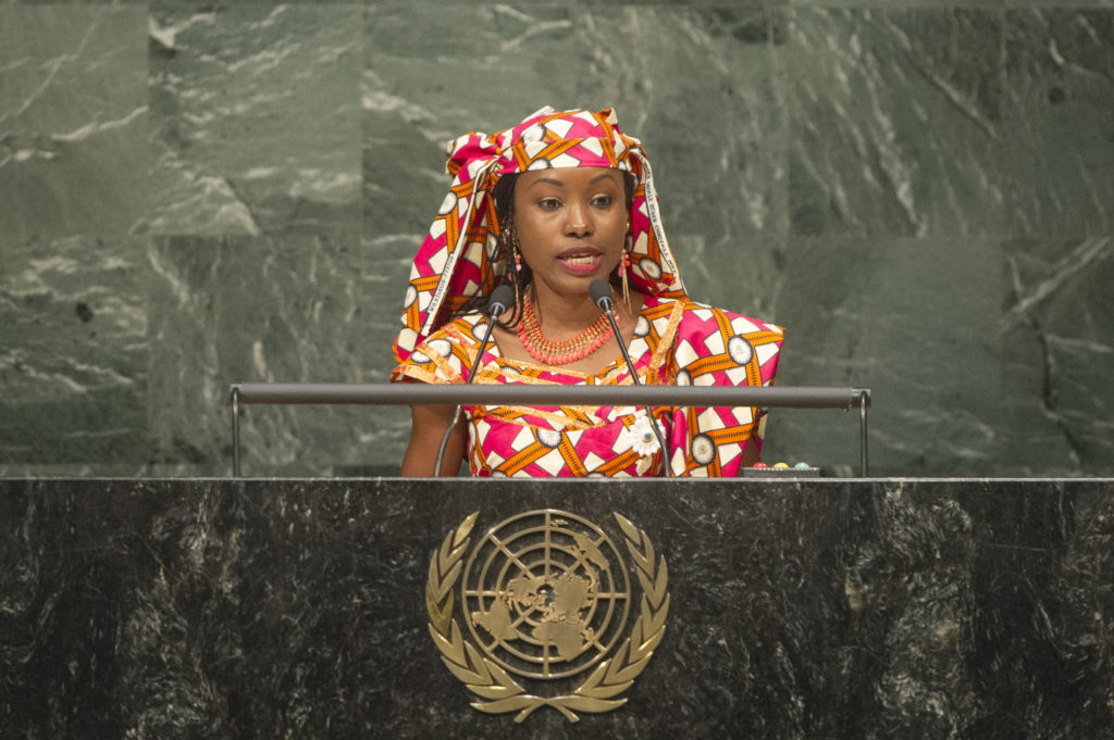 A black woman, wearing a dress and matching headscarf in a red, white and orange pattern, is speaking from a lectern, upon which  is the emblem of the United Nations.