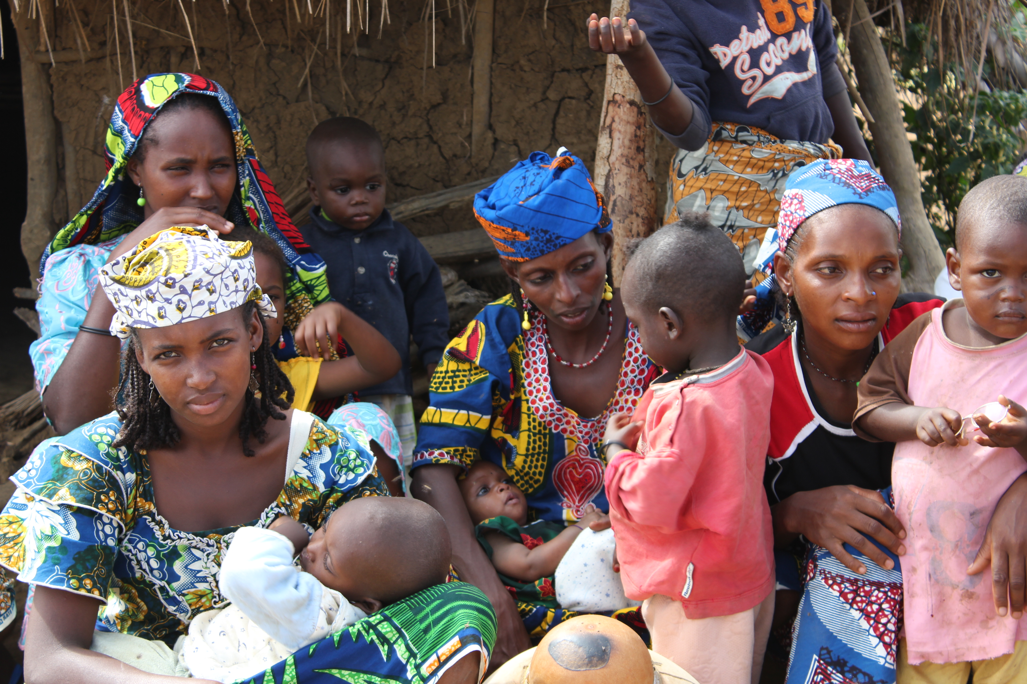 A group of four black women, wearing colorful dresses and headscarves, are taking care of five children. The woman in the bottom left corner of the photo is looking at the camera while holding a sleeping baby. Behind her, another woman, a blanket on her head, wearing a green earring, holds a child in her lap. Next to them is another woman holding a child, while talking to another who is standing and looking at her. Another woman, in the right corner of the picture, is hugging a child, who is standing, looking at the camera, wearing a pink and brown t-shirt.