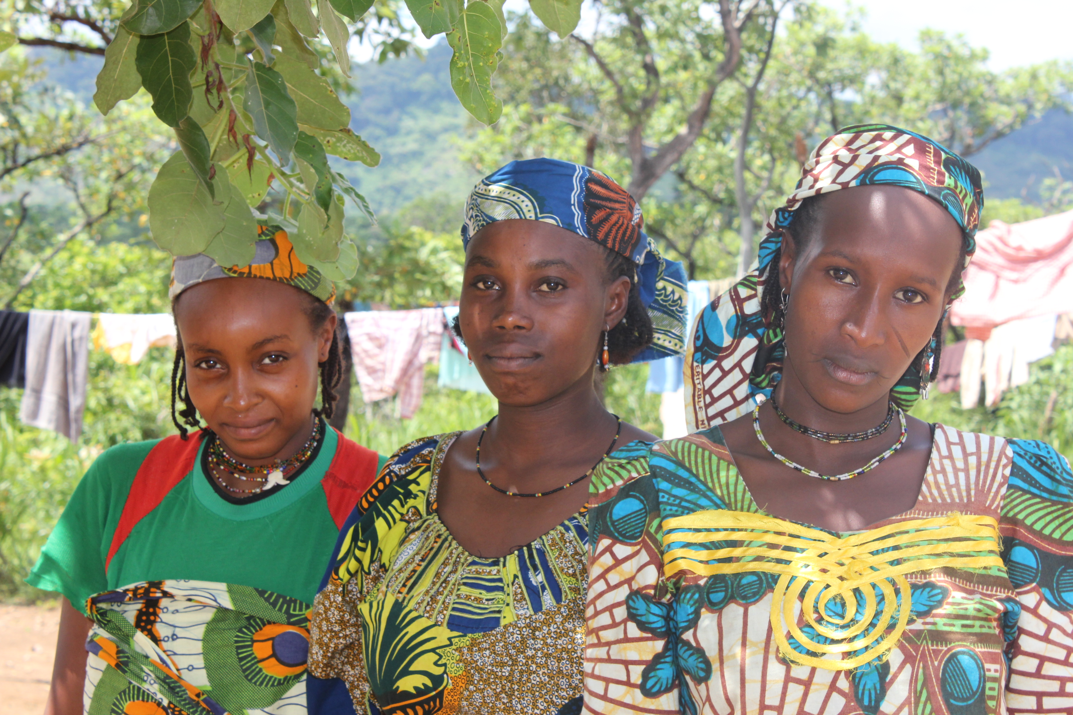 Three young black women wearing headscarves, necklaces and colorful dresses, are looking at the camera. Behind, a clothesline with clothes drying on it, and some trees.
