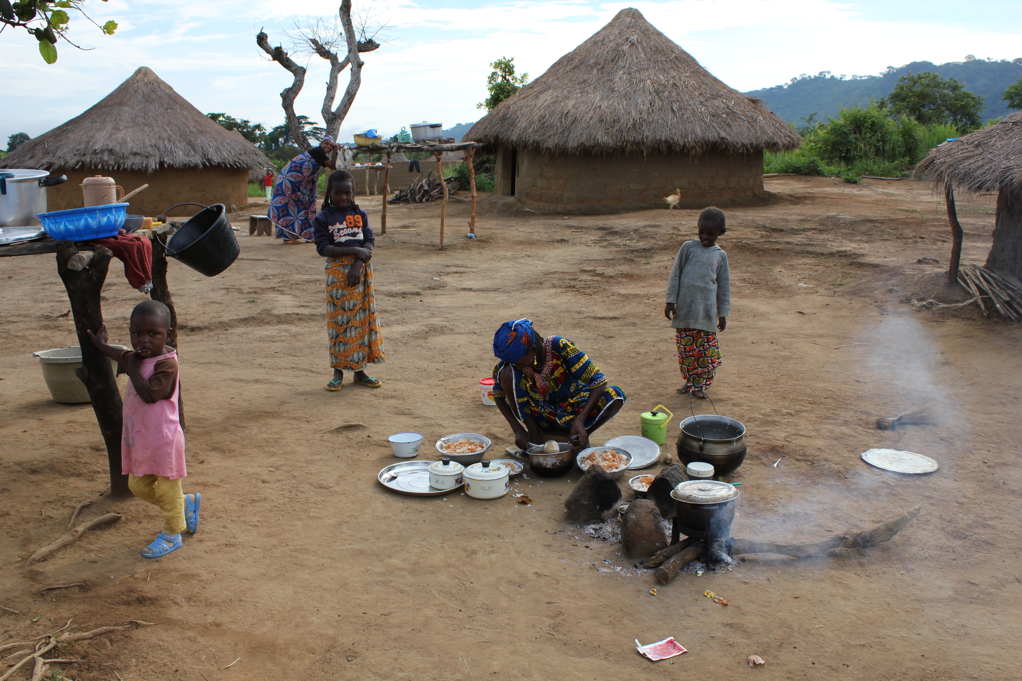 In an arid region, three simple round huts with roofs made of dried palm leaves. In front of them, a black woman cooks on a fire on the ground with simple white crockery (pans and dishes). Two black children stand behind her, watching. A third child, in the front left corner of the picture, is wearing a pink shirt and yellow pants. She is looking at the camera, holding the base of an improvised wooden table.